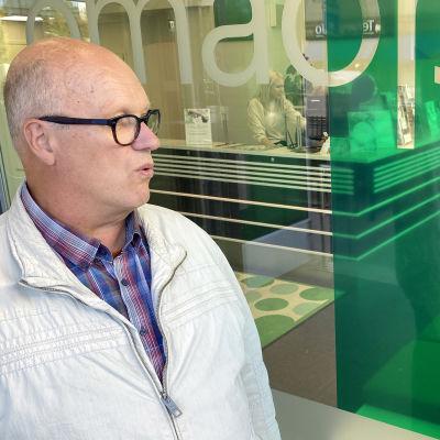 Jukka Kuivaniemi ja Anu Iso-Kokkila-Vähänen keskustelevat pankin ulkopuolella taustallaan pankin ikkunat, joista näkee pankin vastaanottotiskille.
