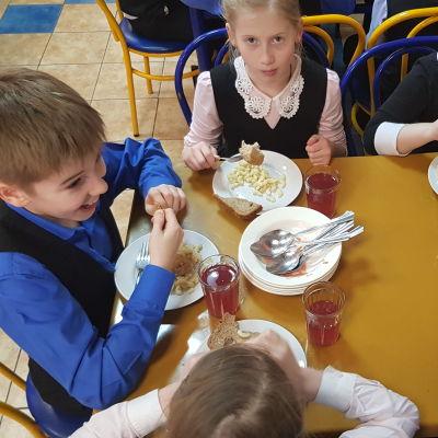Bild ovanifrån av ryska barn som äter skolmat.