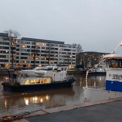 En blåvit sjöbuss, M/S Hamnskär, åker förbi en annan sjöbuss, M/S Jaarli, i Aura å i Åbo en smådimmig morgon.