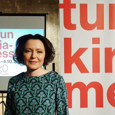 """en kvinna står bredvid en stor skylt med texten """"åbo bokmässa"""" på, på finska."""