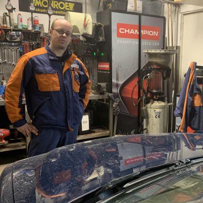 En mekaniker står i en verkstad framför en en bil med öppen huv.