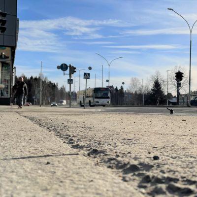 Yleiskuva kadusta Kajaanin keskustassa. Harjaamattoman kadun pinnassa näkyy hiekkakerros.