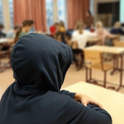 En elev sitter med huvan uppdragen på sin mörkblå munkjacka, långt borta från den övriga klassen.