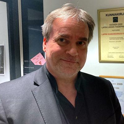 Lapin kamariorkesterin taiteellinen johtaja John Storgårds seisoo kamariorkesterin saamien palkintojen ja kunniakirjojen edessä
