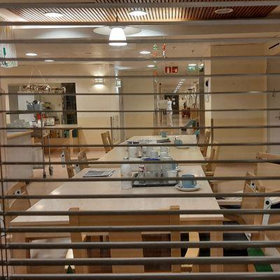 Man kan titta in genom persiennerna till matsalen och korridorerna i ett äldreboende, men under corinaviruspandemin är det förbjudet att besöka vårdhemmet.