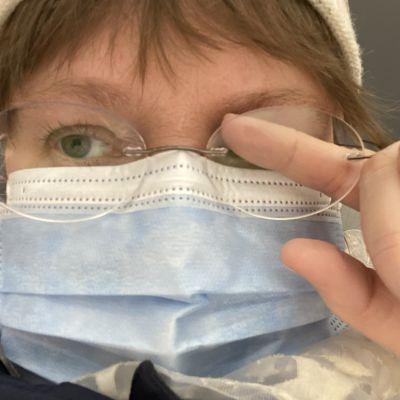 Kuvassa maskia käyttävä nainen pyyhkäisee huurtunutta silmälasin sisäpintaa sormella.
