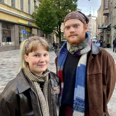 Två unga personer står mitt på gågata och tittar in i kameran