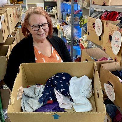 Hopen vapaaehtoistyöntekijä Anja Salmi tutkimassa avustuslaatikon sisältöä.