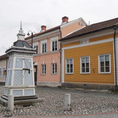 En ljusblå brunn står mitt på den stenlagda gatan mellan trähus i Gamla Raumo.