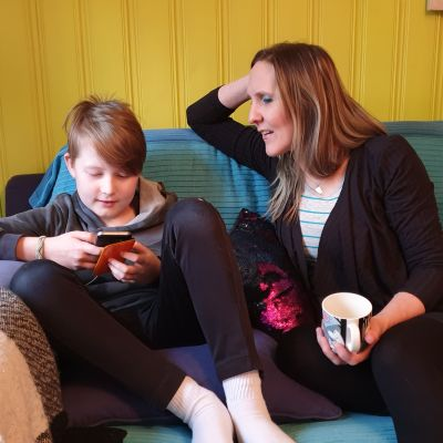 Poika ja äiti istuvat sohvalla ja katsovat pojan kännykkää