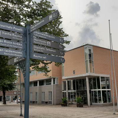 En informationsskylt med vägvisning står utanför Raumos stadshus, ett hus med gulbruna tegel och glasdörrar.