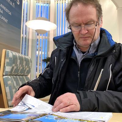 Kuvassa mies lukee lehteä