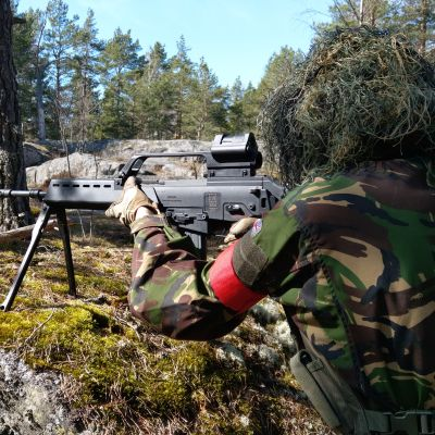 En airsoftspelare siktar med sitt vapen.