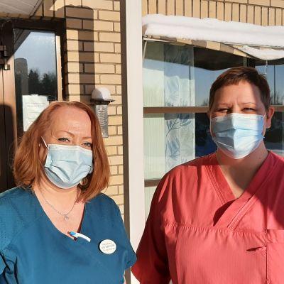 Två hälsovårdare med munskydd vid ingången till en hälsocentral, Carola Silander-Lehtinen i blå sköterskedräkt och Camilla Rautanen i röd sköterskedräkt.