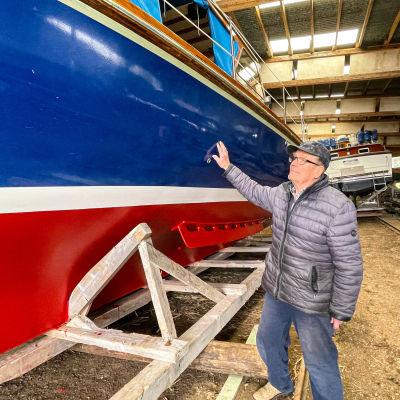 En man vid en båt som är inne i ett varv.