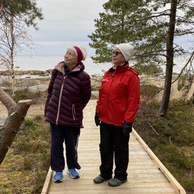 Pietarsaaren vammaisneuvoston sihteeri Maire Paavola ja liikuntatoimenjohtaja Tove Jansson Fäbodan esteettömällä luontopolulla. Taustalla syksyinen meri ja rantaluonto.