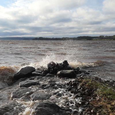 Vesi pärskyy kivilaiturille järven rannalla.