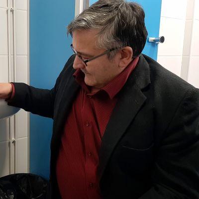 Vaasan ammattikorkeakoulun rehtori Jorma Tuominen tarkastelee lavuaaria, jonka alla kamera oli.