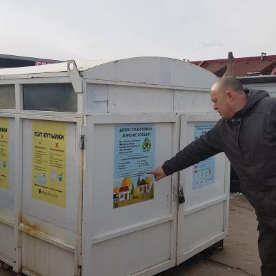 En man pekar på en container för sopor.