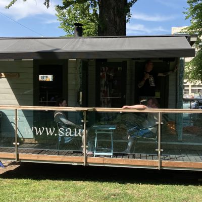 Kaksi asunnotonta saunoo tilapäissaunassa.