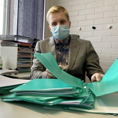 Hallintojohtaja Henri Pätsi selaa Puolangan kunnalle lähetettyjä asiatonta tekstiä sisältäviä asiakirjoja.