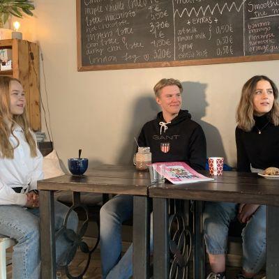 Fyra ungdomar sitter på ett café och dricker kaffe vid ett bord.