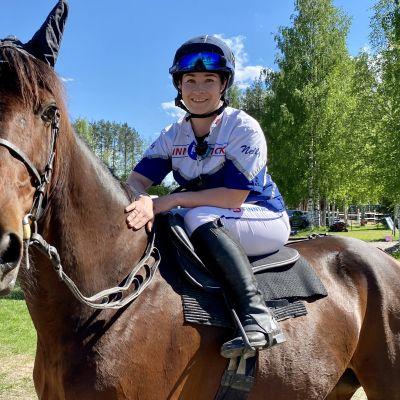 Monteohjastaja Nelly Korpikoski työpaikallaan, eli hevosen selässä.