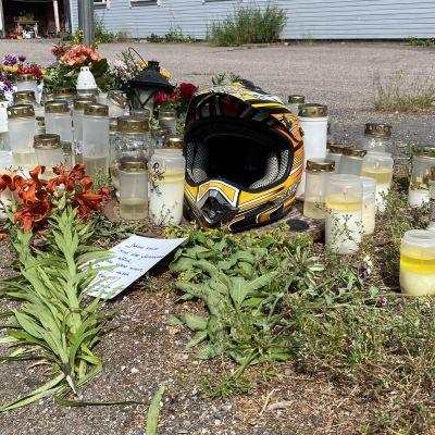 Tienvarren muistopaikalla on moottoripyörän kypärä ja paljon hautakynttilöitä sekä kukkakimppuja.