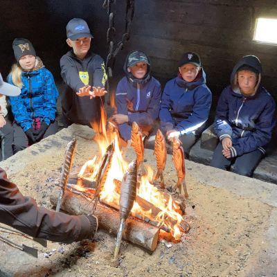 Mies paistaa kodassa siikaa tulella ja ympärillä istuu koululaisia.