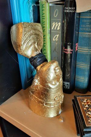 kultainen Nefertitin rintapatsas seisoo päällään kaula murtuneena