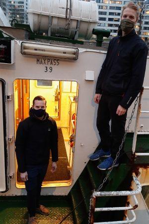 Gustav Ramberg och Jonas Skrifvars, två unga män med munskydd, står då däcket och i en lejdare ombord på en sjöbuss en vintermorgon.