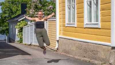 Malin Valtonen hoppar och ser glad ut på en gata, omringad av äldre hus.
