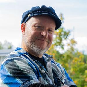 Mikko Kaukolampi hymyilee ulkona kameralle kädet puuskassa.
