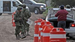 Soldater granskar bilar i jakten på den förrymde knarkbaronen Joaquín Guzmán.