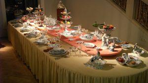 Långt präktigt middagsbord dukat med fina kärl av tyskt Meissenporslin.