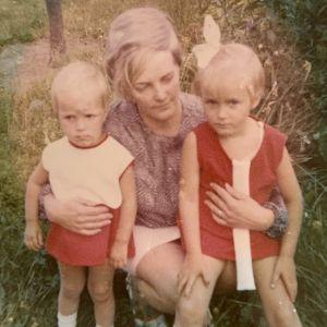 Tanssija Mari Rosendahl pikkutyttönä sisarensa kanssa äidin sylissä pihamaalla poseeraamassa.