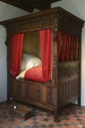 Italiensk hög säng i trä med röda draperier som man måste klättra upp i.