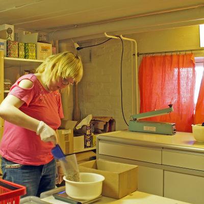 Tuovi Mannström paketerar varor på Vegana i Jakobstad. Hon får inte en vanlig lön, men en så kallad flitpeng som är anspråkslös.