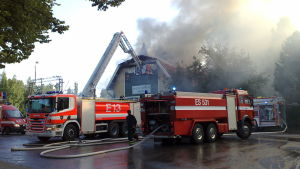 Flera brandbilar och brandmän i släckningsarbete vid Grankulla järnvägsstation.