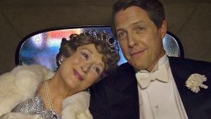 Festklädda Meryl Streep och Hugh Grant lutar sig kärleksfullt mot varandra i baksätet på en bil.