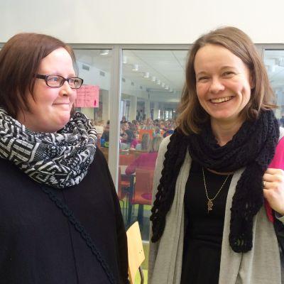 Två lärare, Jessica McQuade och Minttu Manninen, står framför ett fönster till skolas matsal.
