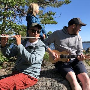 Pasi Hiihtola, Mikael Grönroos och Livs sitter på en strandsten
