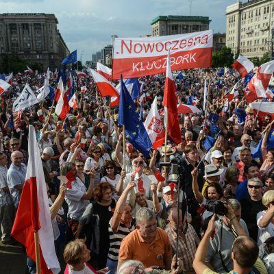 Tusentals demonstranter med Polens rödvita flagga och Eu:s blåa flagga med gula stjärnor demonstrerar i Warszawa.