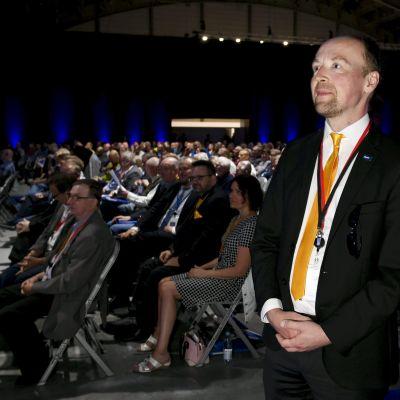 Jussi Halla-aho på Sannfinländarnas partimöte med publiken i bakgrunden.