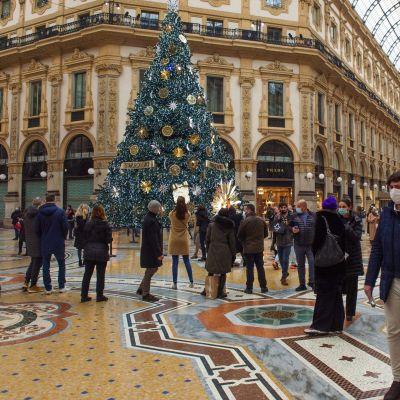 Julshopping i Milan. På bild flera människor i en köphall. I mitten står en stor julgran.