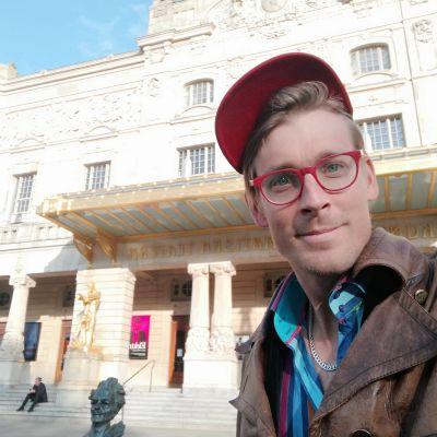 En man i röd keps tar selfie framför ett stort beigehus, Dramaten.