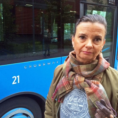 Allvarlig kvinna; Annamari Auermaa med HRT:s buss i bakgrunden.