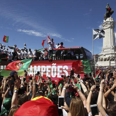 Portugals guldhjältar på ett bussflak i ett folkhav.
