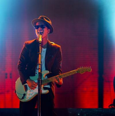 Bruno Mars på scenen med gitarr och solglasögon.