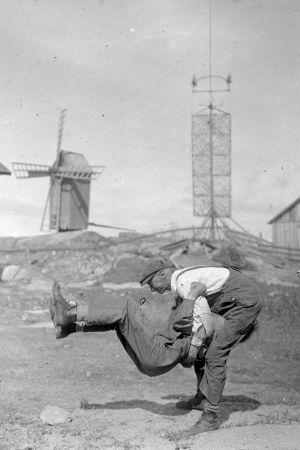 """Två män leker leken """"prova styrka"""", där den ena ska lyfta upp den andra. Bilden är tagen 1933 på Björkö, Åland."""